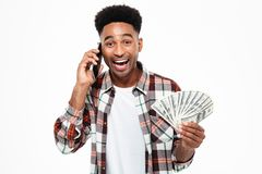 Portrait of an excited satisfied african man. Holding bunch of money banknotes while talking on mobile phone and looking at camera isolated over white Royalty Free Stock Images