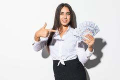 Portrait of an excited satisfied girl holding money banknotes and pointing finger isolated over white background stock photo