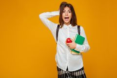 Portrait of an excited schoolgirl holding books. And apple while standing and looking at camera isolated over orange background Royalty Free Stock Photo