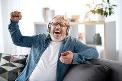 Cheerful mature man listening to music from smartphone. Portrait of excited senior male enjoying favorite song at home. He is singing with passion while wearing Royalty Free Stock Image