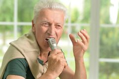 Excited senior man holding  microphone Royalty Free Stock Images
