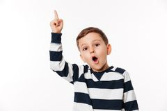 Portrait of an excited smart little kid pointing finger up Stock Photos