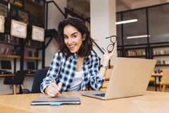 Portrait excited smiled brunette young woman working with laptop in library. Clever student, university life, working in. Internet, smiling to camera, cheerful royalty free stock image