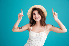 Portrait of a excited summer girl in straw hat pointing Stock Photography