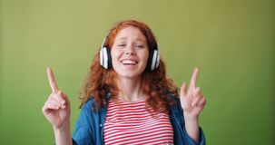 Portrait of excited teenager in headphones dancing chilling listening to music. Having fun alone on green background. Millennials and modern gadgets concept stock video footage