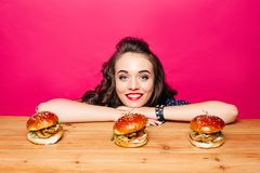 Happy beautiful girl with hairstyle with three burgers on wooden Stock Photography