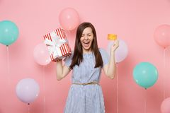Portrait of excited woman with closed eyes in blue dress hold credit card and red box with gift present on pink. Background with colorful air balloon. Birthday royalty free stock photography