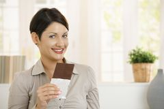 Portrait of excited woman eating chocolate Royalty Free Stock Images