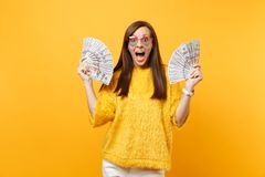 Portrait of excited woman in heart eyeglasses screaming, holding bundle lots of dollars, cash money isolated on bright. Yellow background. People sincere stock photo