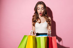 Portrait of an excited woman looking at colorful shopping bags. Portrait of an excited happy woman looking at colorful shopping bags isolated over pink Royalty Free Stock Image