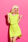 Portrait of excited woman. Smiling blond girl in lime dress gesturing success with fists raised in the air. Three quarter length studio shot on pink background Royalty Free Stock Photography