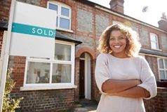 Portrait Of Excited Woman Standing Outside New Home With Sold Sign stock image