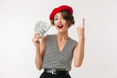 Portrait of an excited woman wearing red beret. Holding bunch of money banknotes and pointing finger up isolated over white background Royalty Free Stock Image