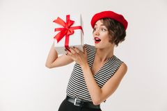 Portrait of an excited woman wearing red beret. Holding present box isolated over white background Royalty Free Stock Photography