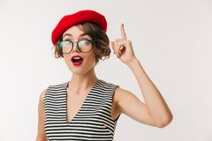 Portrait of an excited woman wearing red beret pointing. Finger up isolated over white background Stock Images