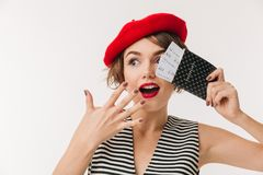 Portrait of an excited woman wearing red beret. Holding passport and celebrating isolated over white background Royalty Free Stock Image