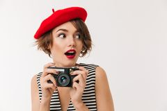 Portrait of an excited woman wearing red beret. Holding photo camera and looking away isolated over white background Stock Photography