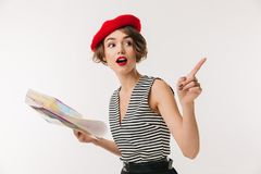 Portrait of an excited woman wearing red beret. Holding travel map guide and pointing finger away isolated over white background Royalty Free Stock Image