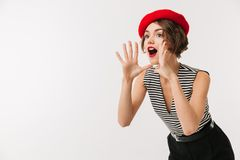 Portrait of an excited woman wearing red beret. Screaming loud isolated over white background Stock Images