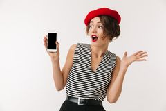 Portrait of an excited woman wearing red beret. Showing blank screen mobile phone isolated over white background Royalty Free Stock Image