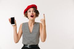 Portrait of an excited woman wearing red beret. Showing blank screen mobile phone and pointing finger up isolated over white background Stock Photos
