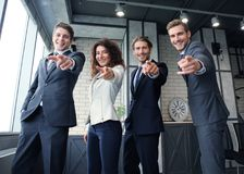 Portrait of excited young business people pointing at you. Royalty Free Stock Image