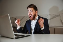 Portrait of an excited young businessman dressed in suit Royalty Free Stock Images