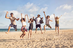 Portrait of excited young friends jumping. On the beach Stock Images