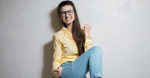Portrait of excited young girl over white background. Dressed in yellow, wearing glasses. stock photos