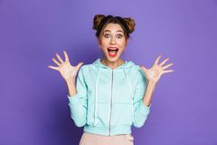 Portrait of excited young girl with two buns screaming and raising arms, isolated over violet background in studio royalty free stock photos