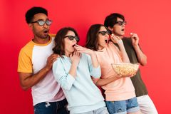 Portrait of an excited young group of multiracial friends. In 3d glasses having fun while standing together with popcorn and pointing away isolated over red Royalty Free Stock Photos