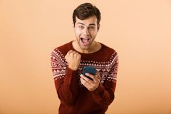 Portrait an excited young man standing. Over beige background, holding mobile phone stock photography