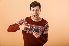 Portrait an excited young man standing. Over beige background, pointing finger at mobile phone royalty free stock photos