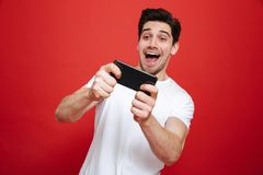 Portrait of an excited young man in white t-shirt playing. Games on mobile phone  over red background Stock Image