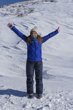 Portrait of an excited young woman with arms up in the snowed mo Royalty Free Stock Photo