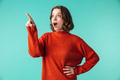 Portrait of an excited young woman dressed in sweater. Pointing finger away isolated over blue background Royalty Free Stock Photography