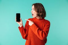 Portrait of an excited young woman dressed in sweater. Pointing finger at blank screen mobile phone isolated over blue background Royalty Free Stock Photo