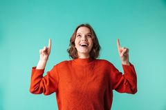 Portrait of an excited young woman dressed in sweater. Pointing fingers up isolated over blue background Stock Photos