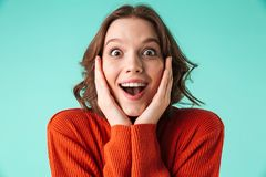 Portrait of an excited young woman dressed in sweater. Looking at camera isolated over blue background Royalty Free Stock Images