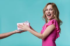 Happy girl receiving present box in male hand royalty free stock photography