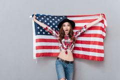 Portrait of an excited young woman holding USA flag Stock Photos