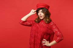 Portrait of excited young woman in lace dress holding cap, keeping mouth open looking aside isolated on bright red stock photos