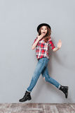 Portrait of an excited young woman in plaid shirt jumping Stock Photo