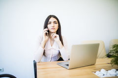 Portrait of executive financial woman sitting at desk and working on laptop while making call in office. Portrait of executive financial woman sitting at desk Stock Photography