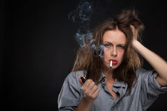 Portrait of exhausted female holding cigarette. Stock Images
