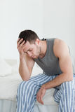 Portrait of an exhausted man sitting on his bed Royalty Free Stock Photo