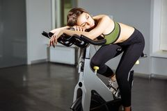 Portrait of exhausted woman spinning pedals on exercise bike royalty free stock photography
