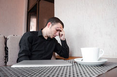 Portrait of exhausted worker in black shirt sleeping on his desktop in cafe with cup of coffee. Royalty Free Stock Image