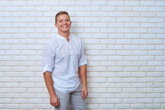 Portrait of exhilarated young man against brick wall with fashio. Mid portrait of exhilarated young man against brick wall with fashion look Royalty Free Stock Photos