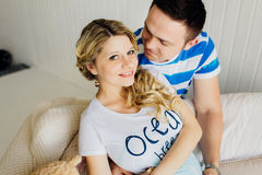 Portrait of expecting couple laughing happily at camera, embracing baby in belly together. Stock Images